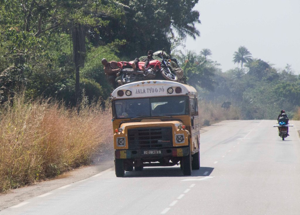 Overloaded old school bus with motorbike and man on roof!